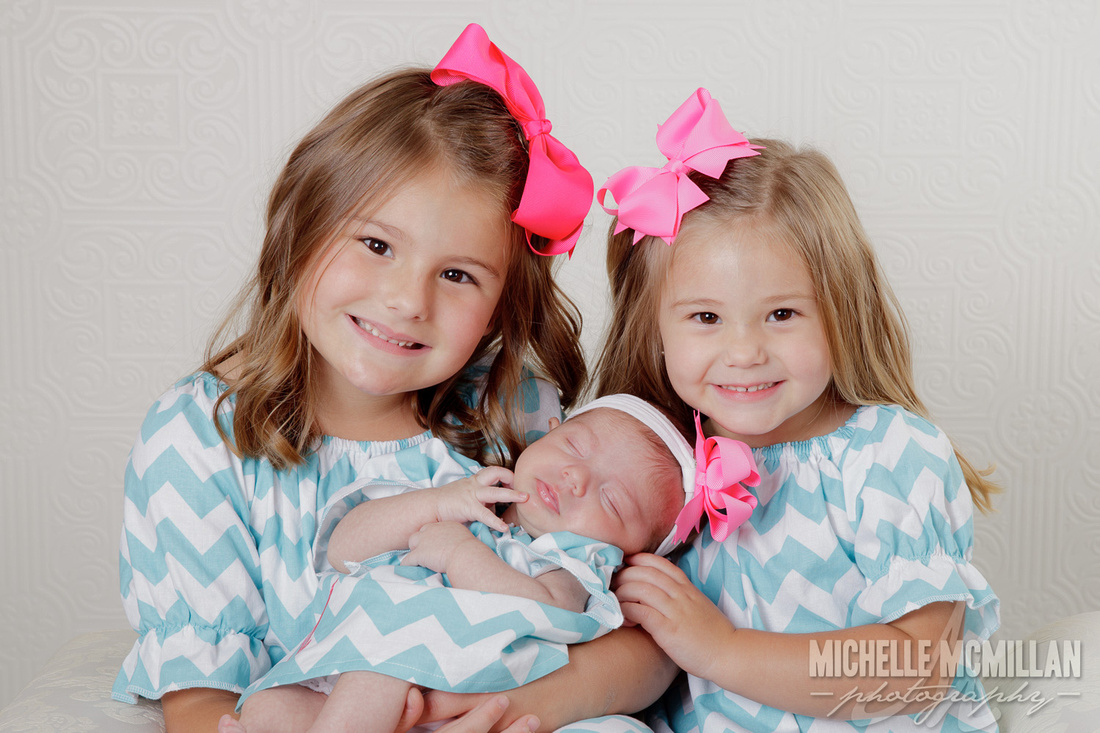 newborn with sisters